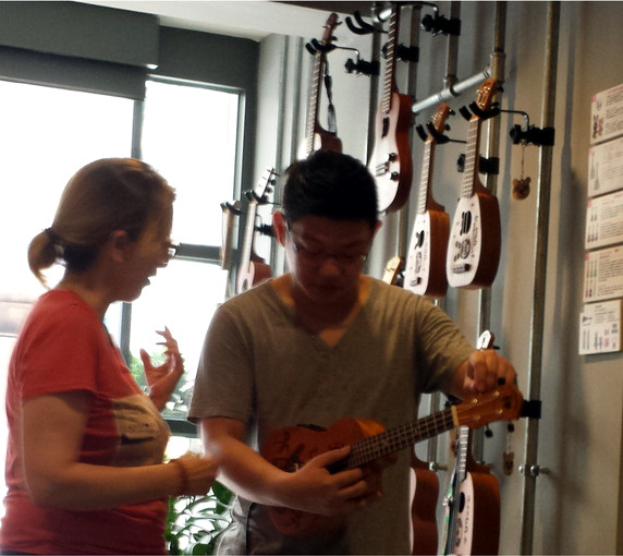 The author testing a ukelele with Johnson Liu. Photo by Laura Miller