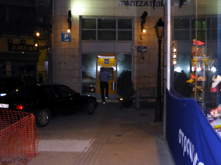 ATM Safari for Cash 27/06/2015 10:30pm, Chalkida, Greece. Looking desperately for cash the next day after the referendum. Note the car, the engine on while the driver checks if the ATM has cash or not. Photo by Stamatis Amarianakis.