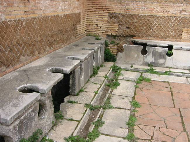 The ancient Romans had sanitation figured out, but were a bit low on privacy. Photo by Fubar Obfusco (en.wiki) [Public domain], via Wikimedia Commons.