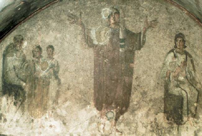 An image from the Catacomb of Priscilla. This woman has her arms outstretched as if holding Mass. Image in the public domain, from Wikimedia.