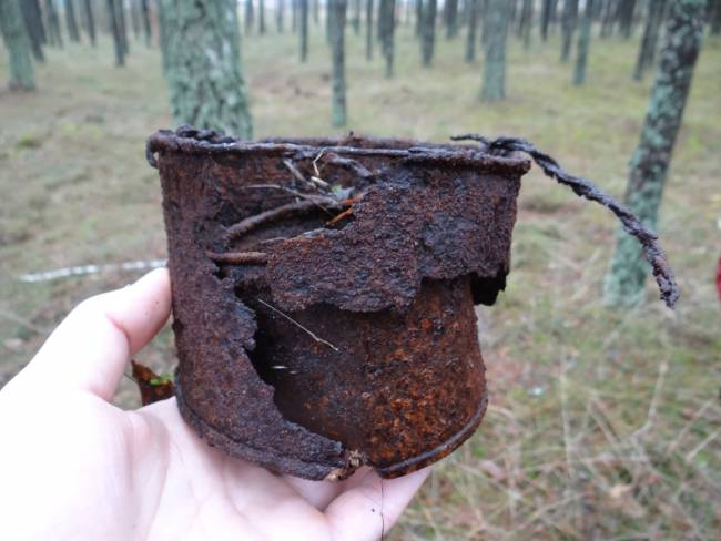 A badly rusted and damaged cup made of a food tin and metal wire. Photo by Dawid Kobiałka.